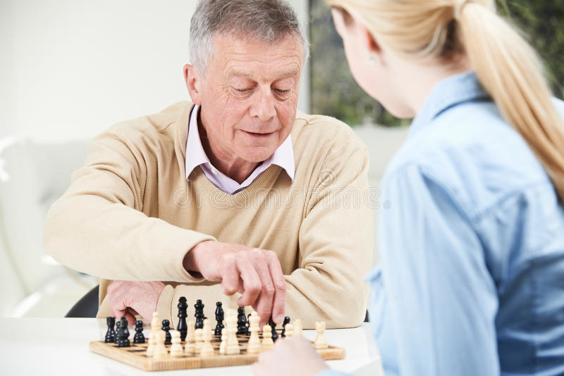 Senior Man Playing Chess With Teenage Granddaughter stock image