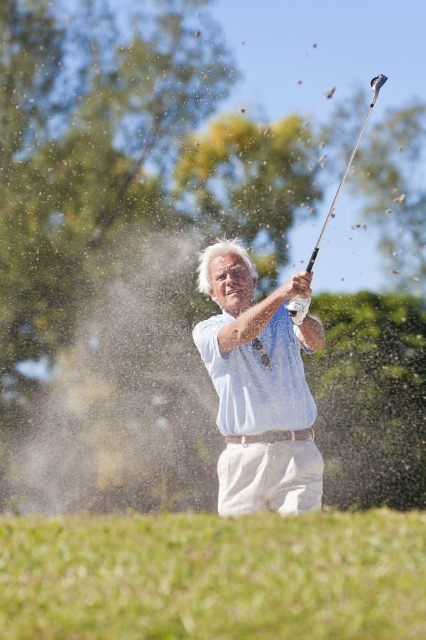 Senior Man Playing Golf Shot In a Bunker stock photo