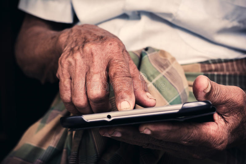 Senior man playing tablet royalty free stock image