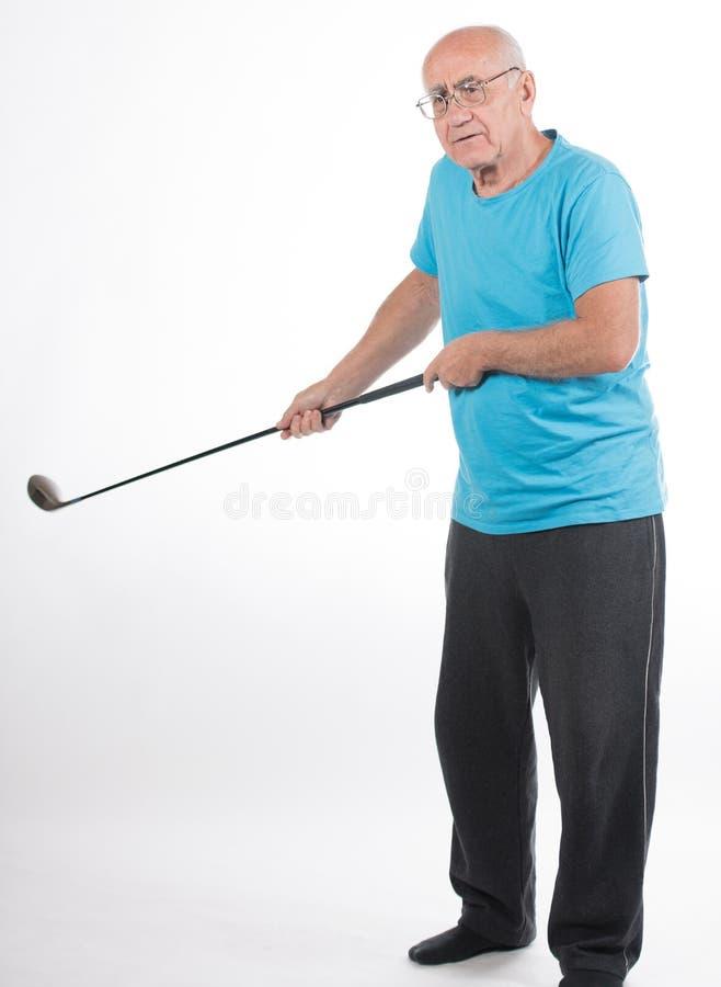Senior man on white background plays golf. Senior man in blue t-shirt on white background plays golf stock photo
