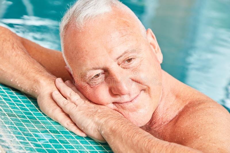 Senior man in the pool dreams about being relaxed royalty free stock image