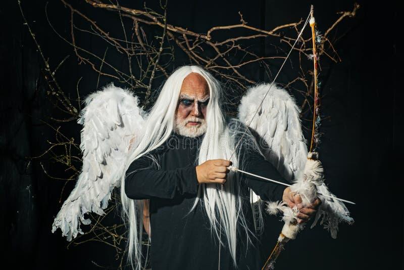 Senior man posing with angel wings. Elderly man holding two red horns. Monster with white blue eyes. Devil horror stock photos