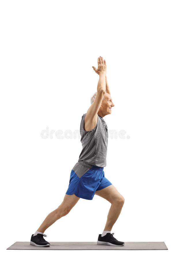 Senior man practicing yoga pose on an exercise mat royalty free stock image