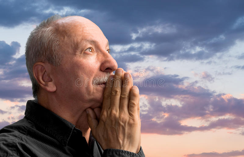 Senior man praying. Against cloudy sky royalty free stock images