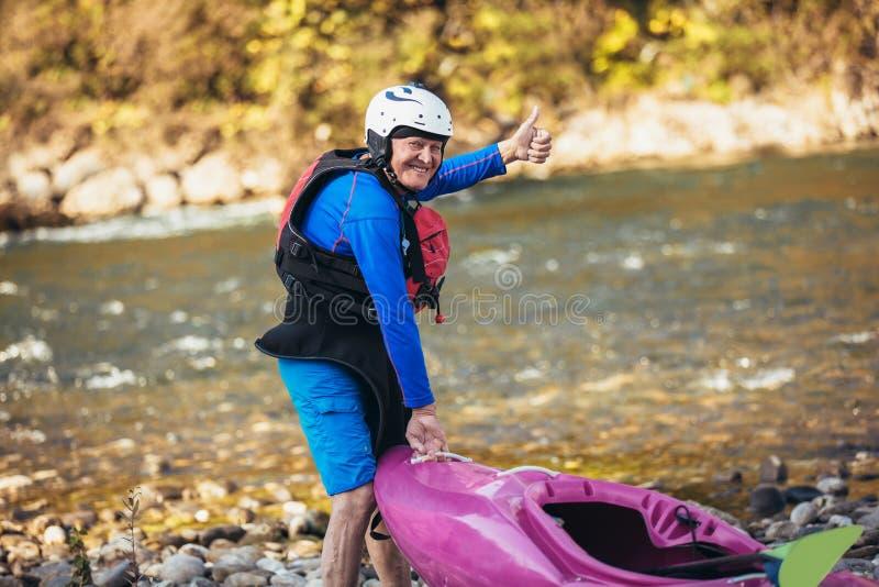 Senior man preparing for kayak tour on a mountain river stock photos