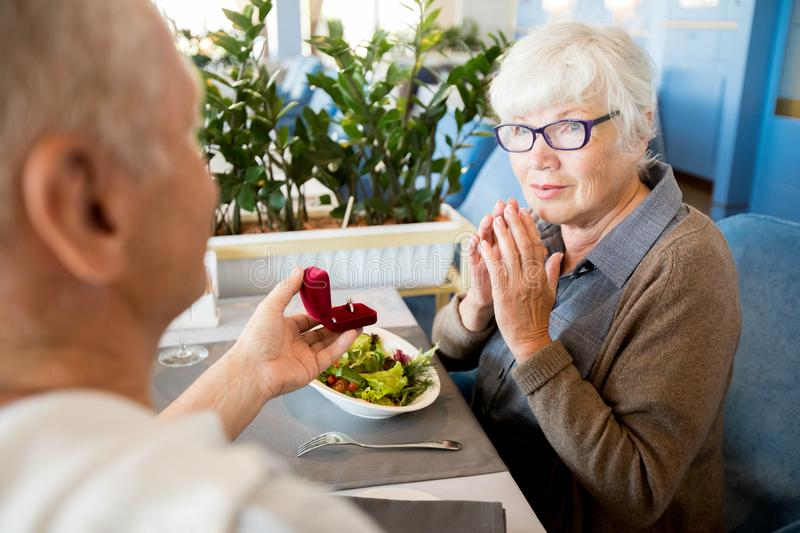 Senior Man Proposing in Cafe. Over shoulder view of senior men proposing to elegant women sitting at table in cafe and looking pleasantly surprised stock photography