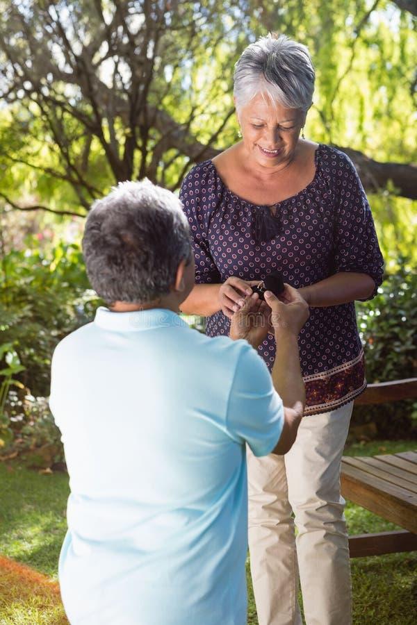 Senior man proposing woman by gifting ring. Senior men proposing women by gifting ring in garden stock photography