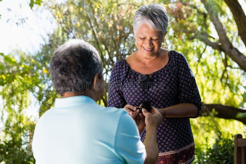 Senior man proposing woman by gifting ring. Senior men proposing women by gifting ring in garden stock image