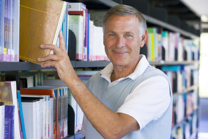 Senior man pulling a library book off shelf.  stock photo