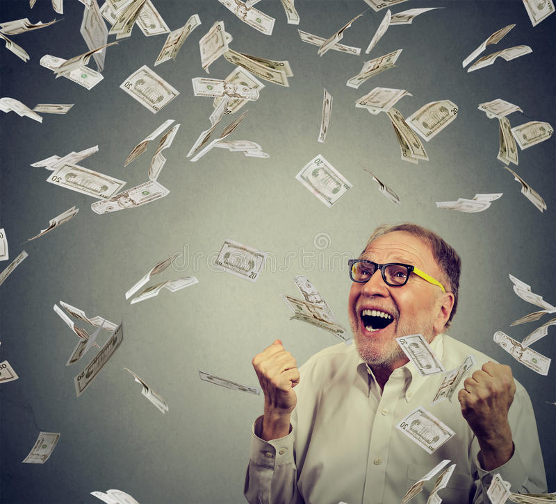 Senior man pumping fists ecstatic celebrates success screaming under money rain stock photos