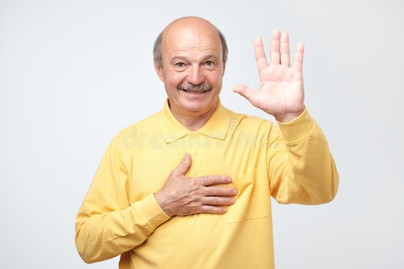 Senior man raising palm and holding hand on chest, promising to me honest. Swear to say truth. Studio shot of sincere happy senior man raising palm and holding stock photo