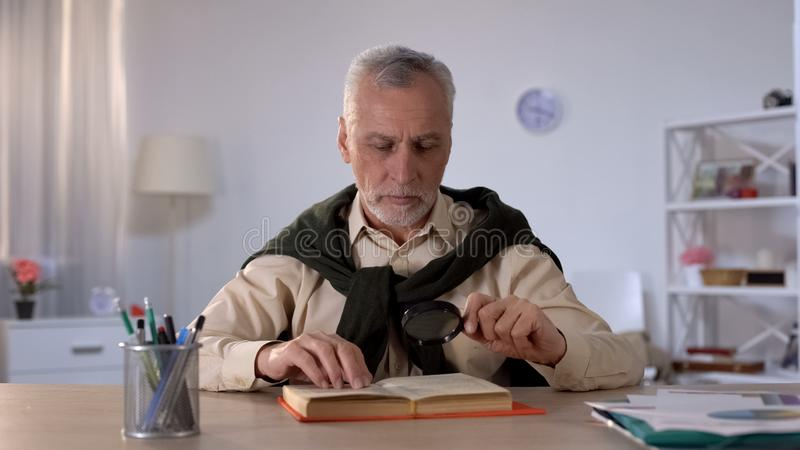 Senior man reading book with magnifying glass, attention to details, erudition. Stock photo royalty free stock photos