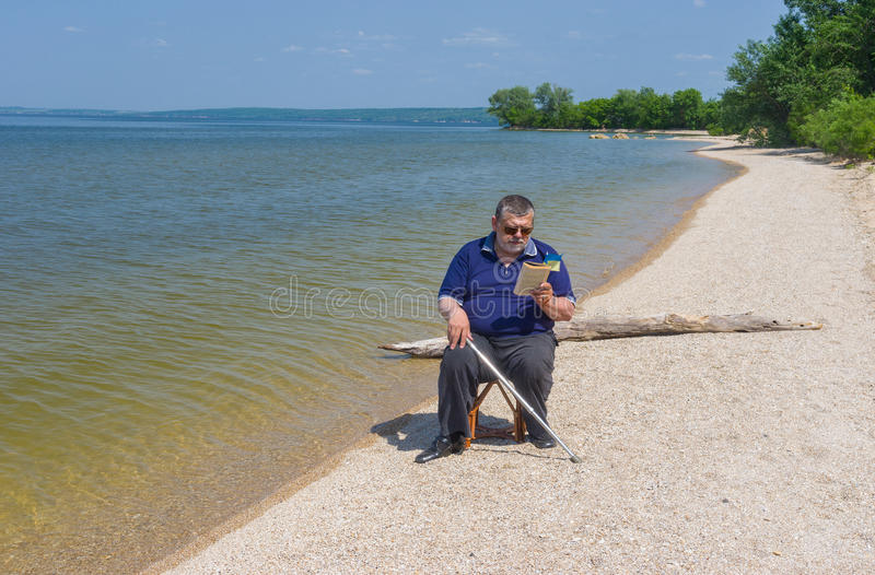 Senior man reading book sitting on a beach of Dnepr river. In Ukraine royalty free stock images