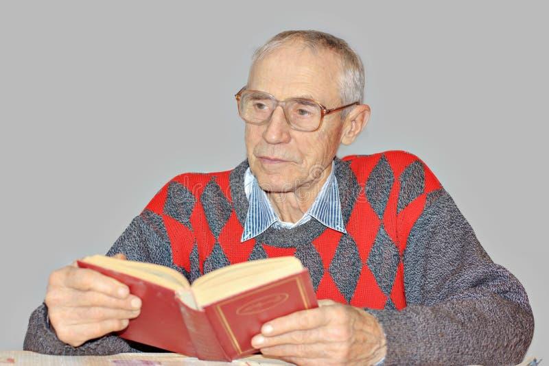 Senior man reading a book at the table royalty free stock photo