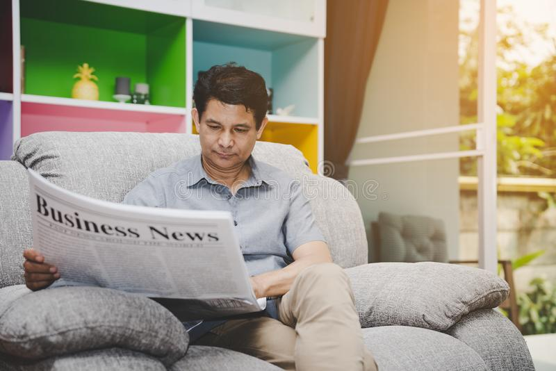 Senior man reading Business News newspaper on sofa in living room at home royalty free stock images