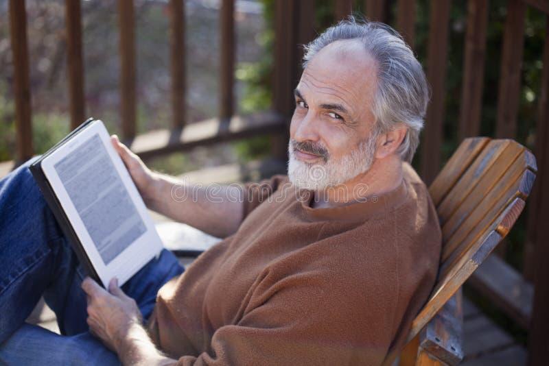 Senior man reading a net book. Senior man using a digital tablet royalty free stock images
