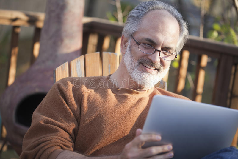 Senior man reading a net book. Senior man using a digital tablet outdoors stock image