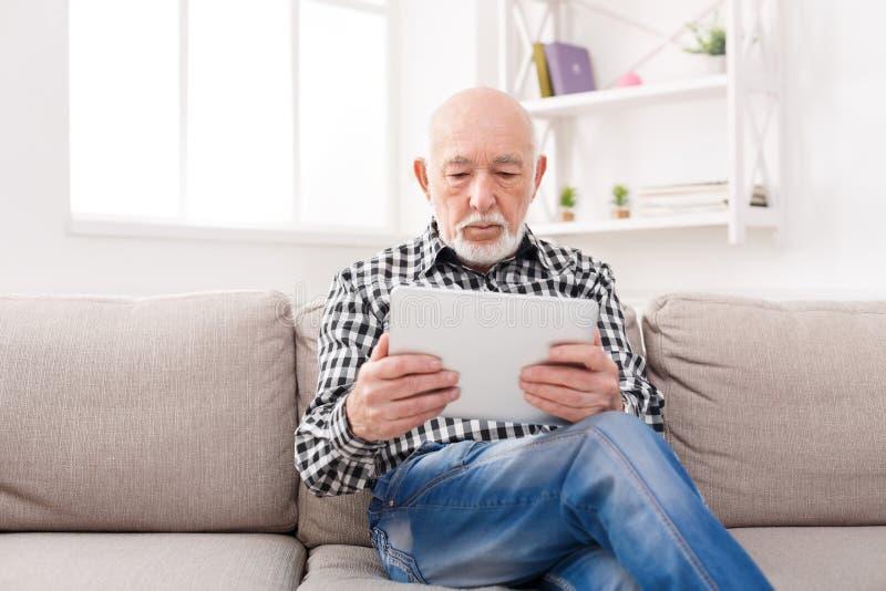 Senior man reading news on digital tablet stock images