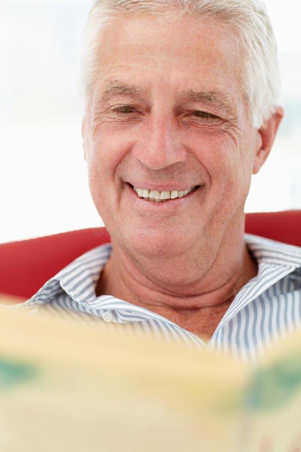 Senior man reading newspaper royalty free stock image