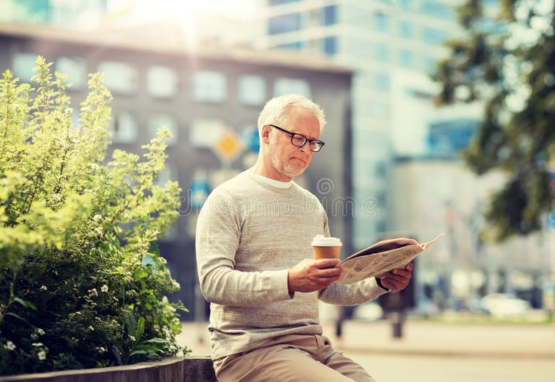 Senior man reading newspaper and drinking coffee royalty free stock photos