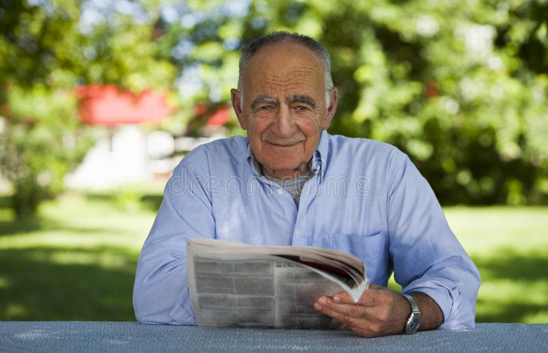 Senior man reading at the park royalty free stock photo