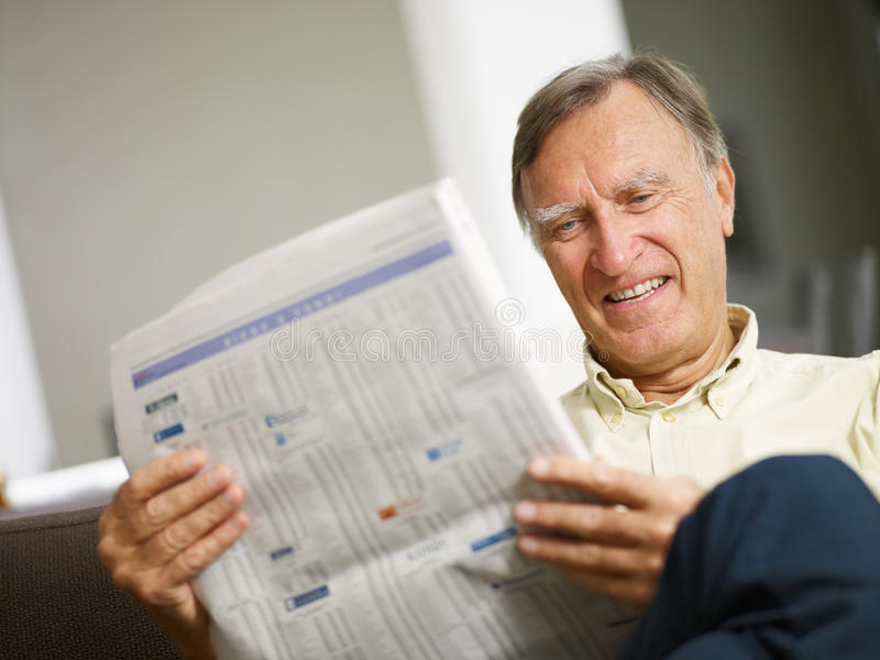 Senior man reading stock listings. And smiling. Copy space royalty free stock photos