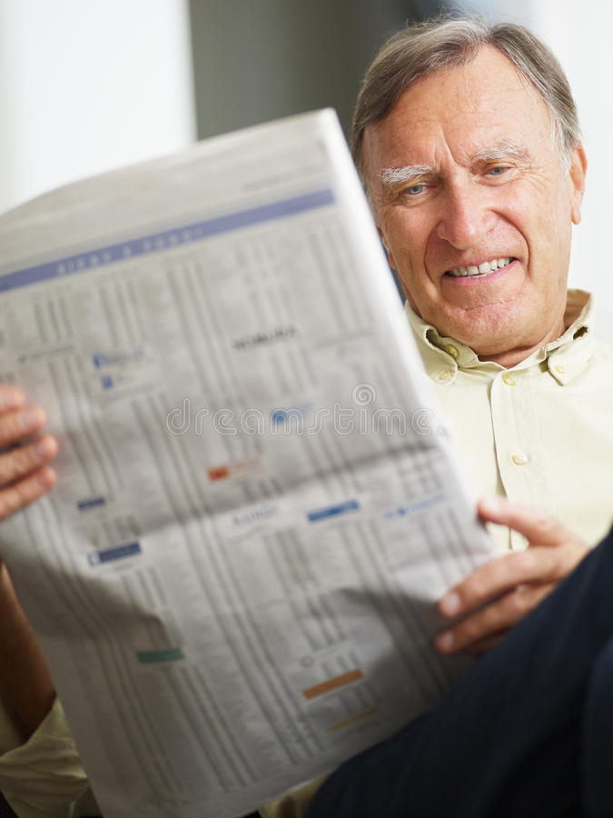 Senior man reading stock listings. And smiling royalty free stock image