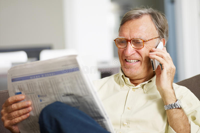 Senior man reading stock listings. And talking on mobile phone. Copy space stock images