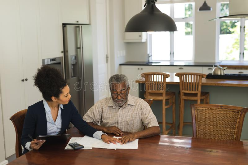 Senior man and real estate agent discussing over documents stock image