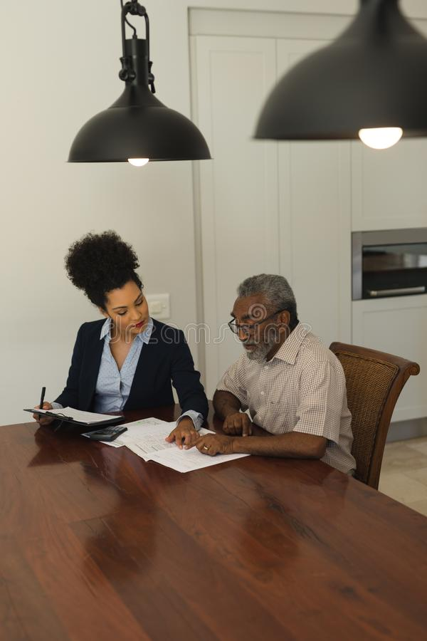 Senior man and real estate agent discussing over documents. Side view of a senior African American men and real estate agent discussing over documents on the royalty free stock photo