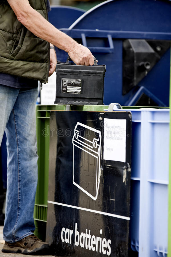 A senior man recycling a car battery, close-up stock image