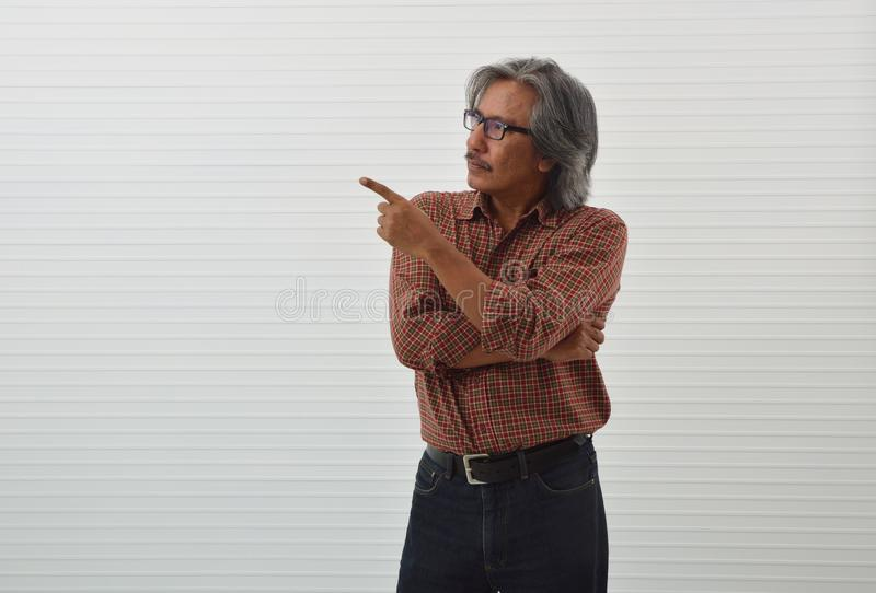 Senior man in red casual shirt, blue jeans and eyeglasses pointing finger up for present something over white wall background stock photo