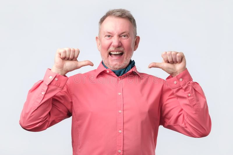 Senior man in red shirt looking confident. With smile on face, pointing oneself with fingers proud stock images