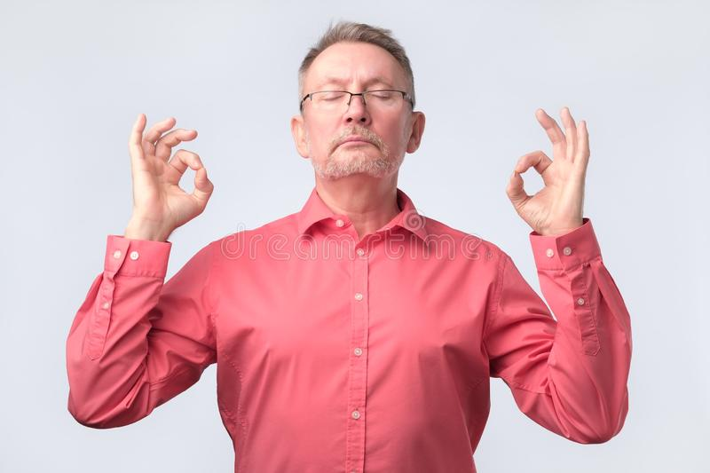 Senior man in red shirt meditates , tries to relax stock images