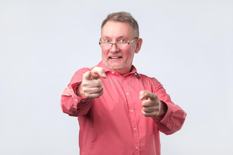 Senior man in red shirt pointing fingers at you royalty free stock image