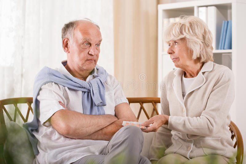 Senior man refusing taking medicament. Photo of senior men refusing taking medicament stock photo