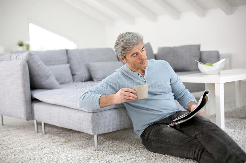 Senior man relaxing at home reading magazine royalty free stock photos