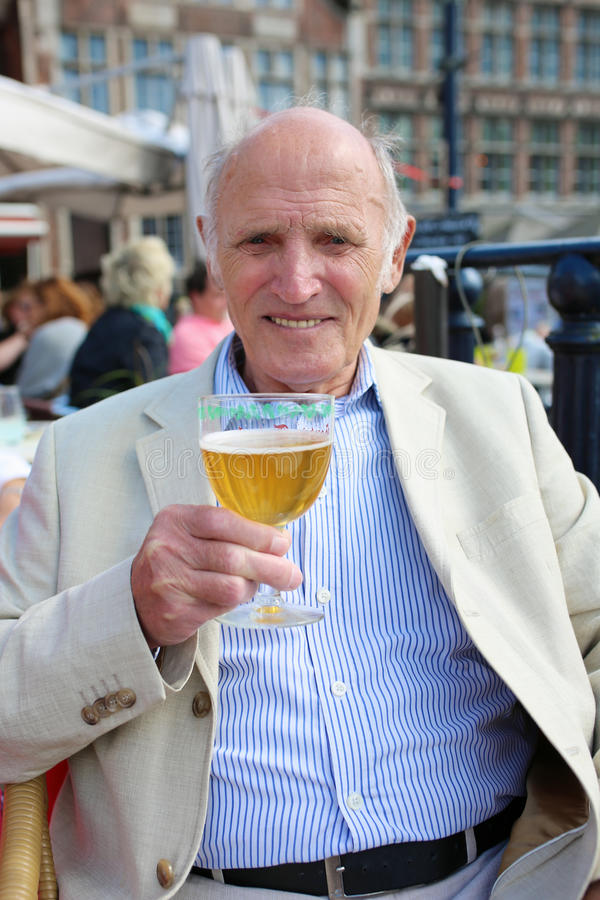 Senior man relaxing in outdoors cafe with drink royalty free stock photo