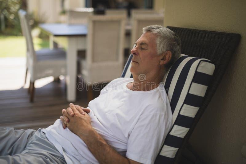 Senior man resting on lounge chair stock photo