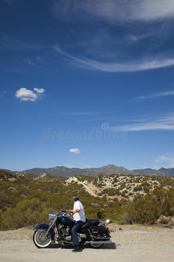 Senior man riding motorcycle on desert road looking to mountains in background. Senior men riding motorcycle on desert road looking to mountains in background stock photo