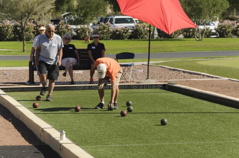 Senior Man rolls ball to play the sport of bocce ball. stock photography