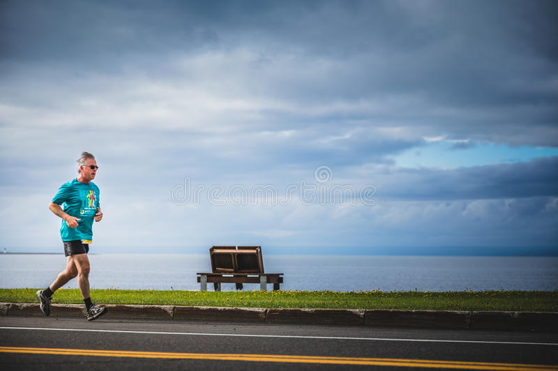 Senior Man Running Alone during the Marathon with Beautiful Ocean Landscape. CARLETON, CANADA - June 4, 2017. During the 5th Marathon of Carleton in Quebec stock photos