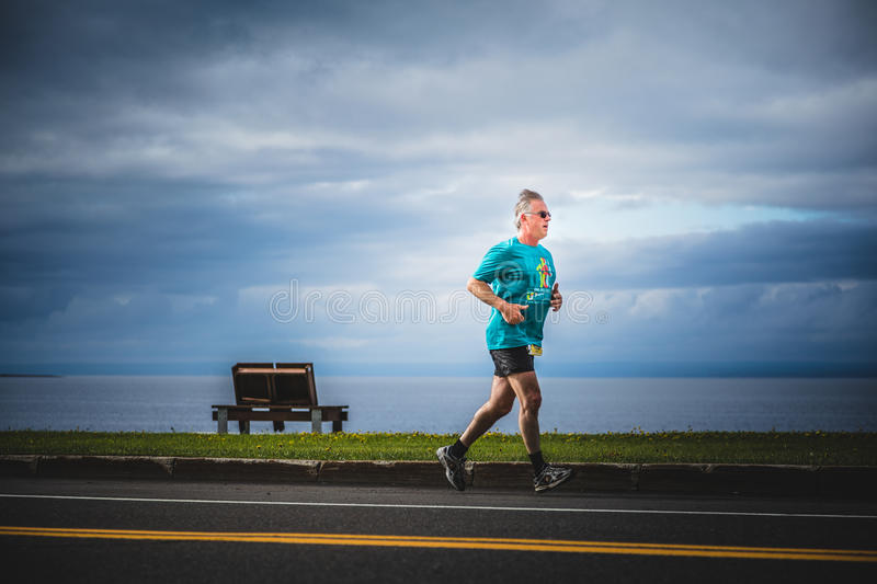 Senior Man Running Alone during the Marathon with Beautiful Ocean Landscape. CARLETON, CANADA - June 4, 2017. During the 5th Marathon of Carleton in Quebec stock image