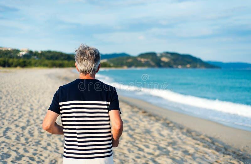 Senior man running on the beach stock images