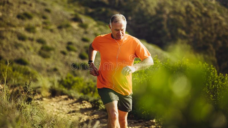 Senior athletic person trail running on a hill stock photos