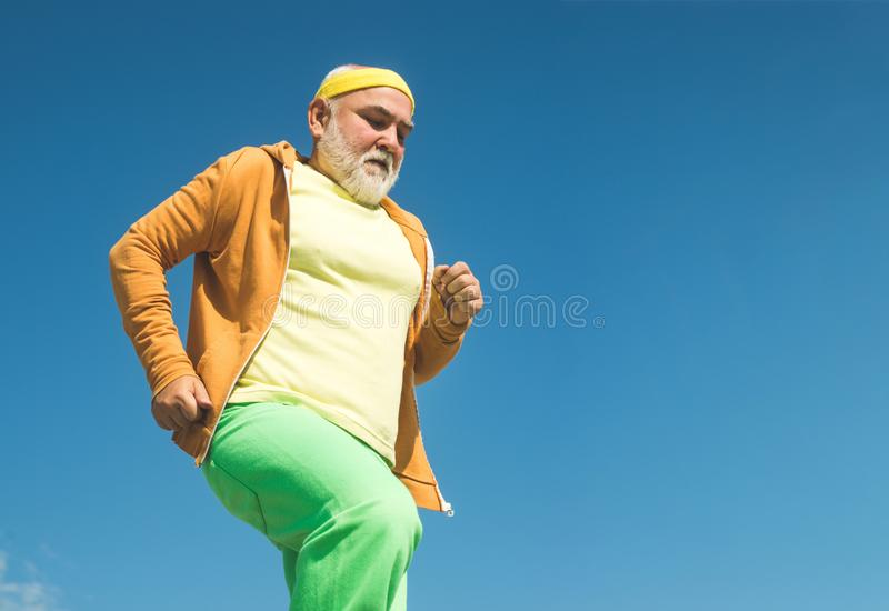 Senior man running in sunny nature. Best cardio workout. Senior fitness person running in park for good health stock photography