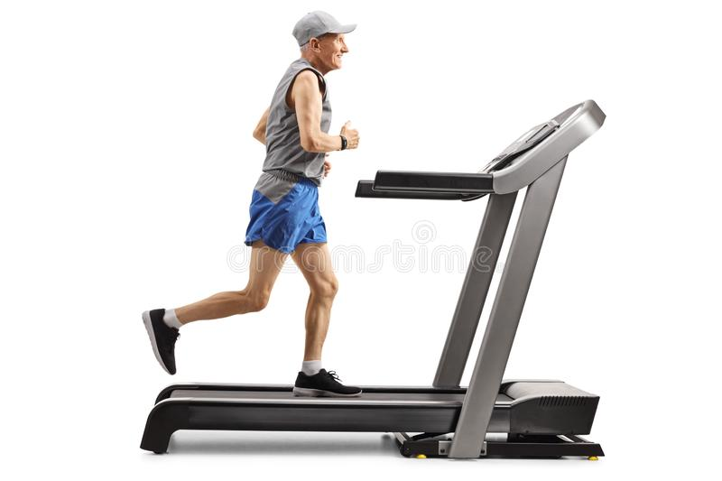 Senior man running on a treadmill and smiling royalty free stock photo