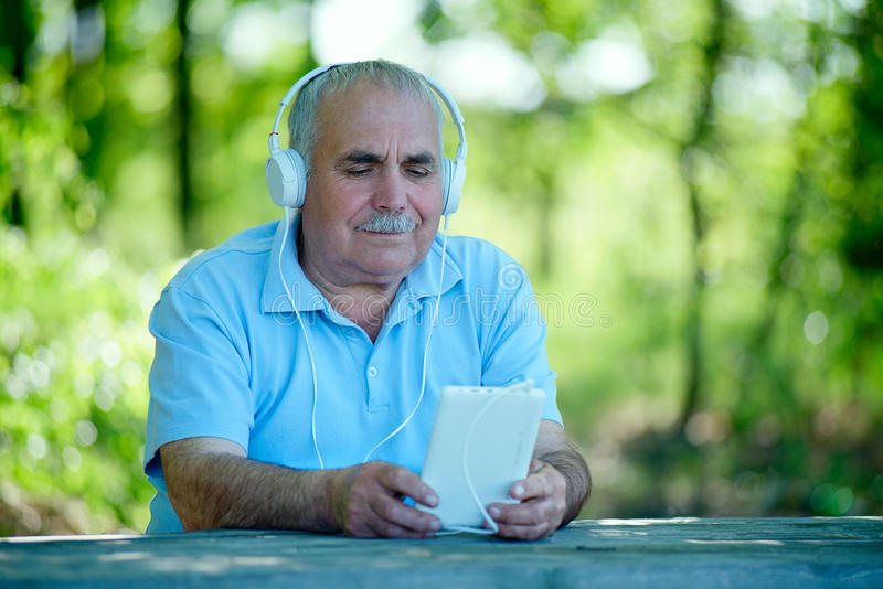 Senior man searching for a tune on his MP3 player. Senior man searching for an online or downloaded tune on his MP3 player or tablet as he sits outdoors in the royalty free stock photography