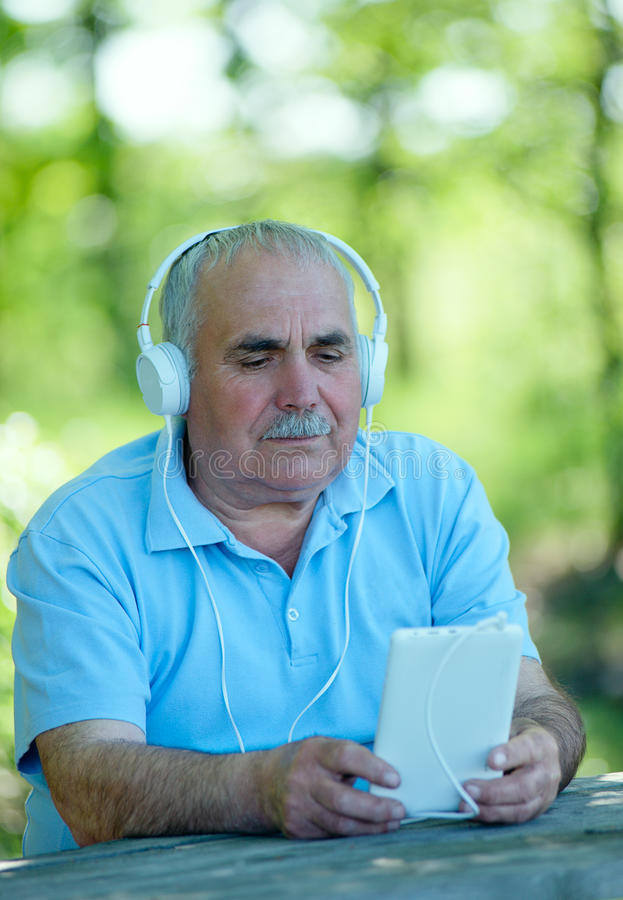 Senior man searching for a tune on his MP3 player. Senior man searching for an online or downloaded tune on his MP3 player or tablet as he sits outdoors in the royalty free stock images