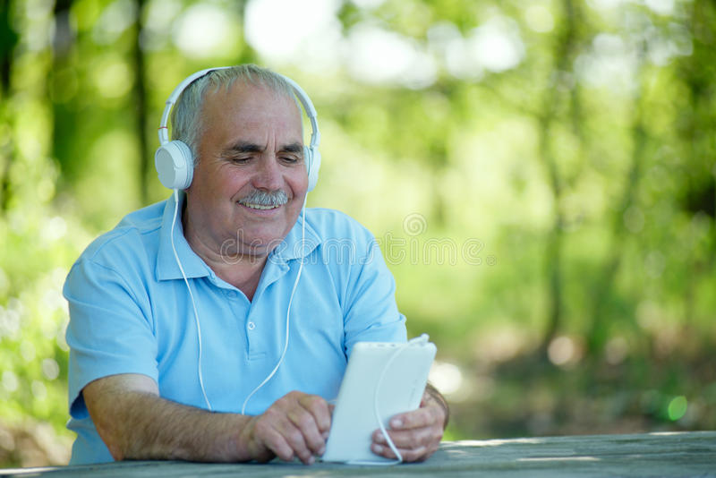 Senior man searching for a tune on his MP3 player. Senior man searching for an online or downloaded tune on his MP3 player or tablet as he sits outdoors in the stock photos